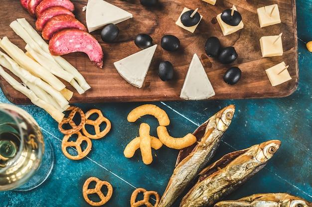Peperoni-scheiben, käse und schwarze oliven, serviert mit trockenem fisch und crackern