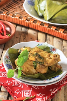 Pepes ayam (pais hayam) ist indonesisches gedämpftes curry-huhn mit traditionellem rezept