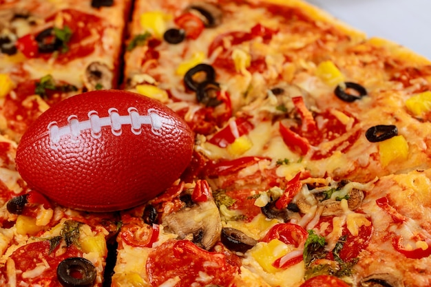 Pepperoni höchste pizza mit fußball für american-football-party.