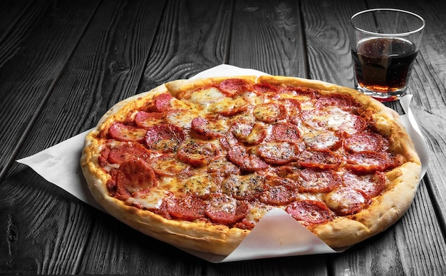 Pepperoni-pizza auf dunkelschwarzem holzbrett, traditionelle italienische pizza, glas cola