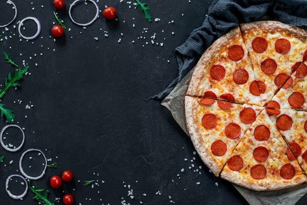Pepperoni-pizza auf schwarzer oberfläche