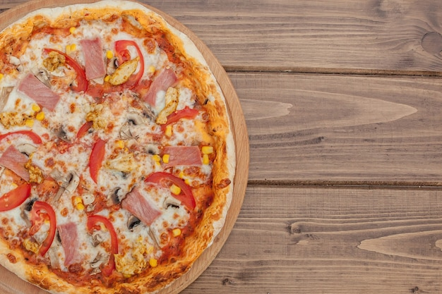 Pepperoni pizza mit mozzarella, schinken, tomaten, pfeffer, gewürzen. italienische pizza.