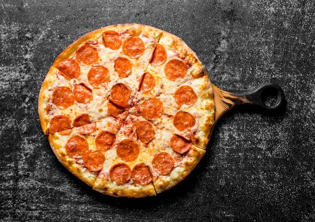 Pepperoni-pizza mit würstchen und käse auf dunklem holztisch