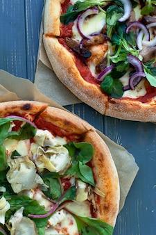 Pepperoni pizza und pizza mit mozzarella, tomaten, pfeffer, oliven, gewürzen und frischem rucola. pizza margherita oder margarita