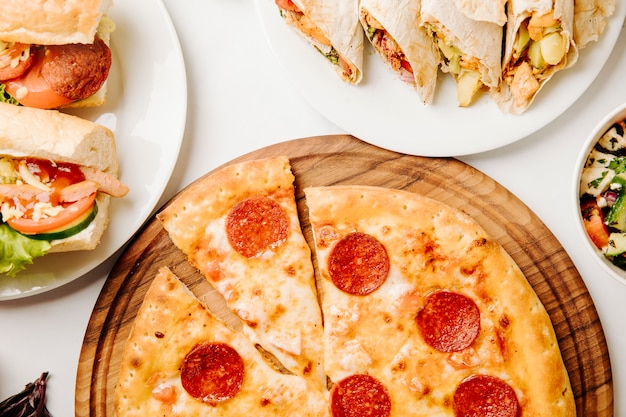 Pepperonipizza, sandwiche, shaurma auf der weißen tabelle.