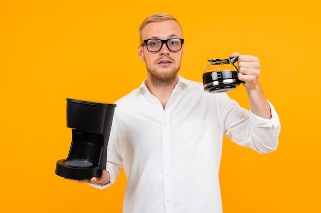 Peppy kerl hält einen vorbereiteten kaffee und eine tasse auf einem gelben hintergrund mit kopienraum.