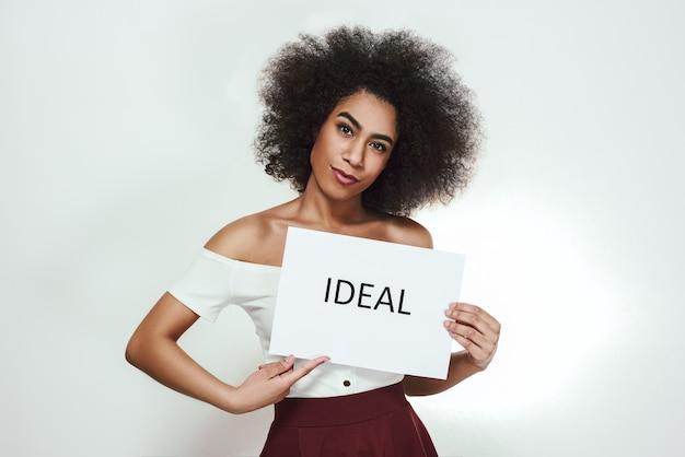 Perfekt in allem studioporträt einer selbstbewussten jungen afroamerikanerin, die ein papier hält, das Premium Fotos