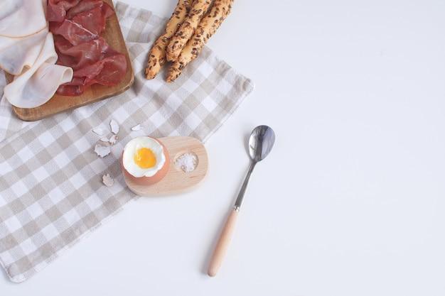 Perfekt serviert frühstück gekochtes ei in hölzernen eierbecher