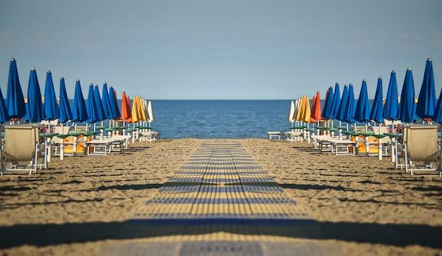 Perfekt spiegelnder und symmetrischer blick auf den strand mit sonnenschirmen und liegen von lignano sabbia d'oro in italien. eine szene ohne menschen, die gefühle der ruhe und des friedens vermitteln, wie es nur das meer tun kann.