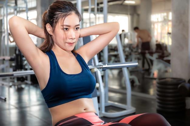 Perfekte asiatin im sportkleidungstraining sitzen oben an der eignungsturnhalle.