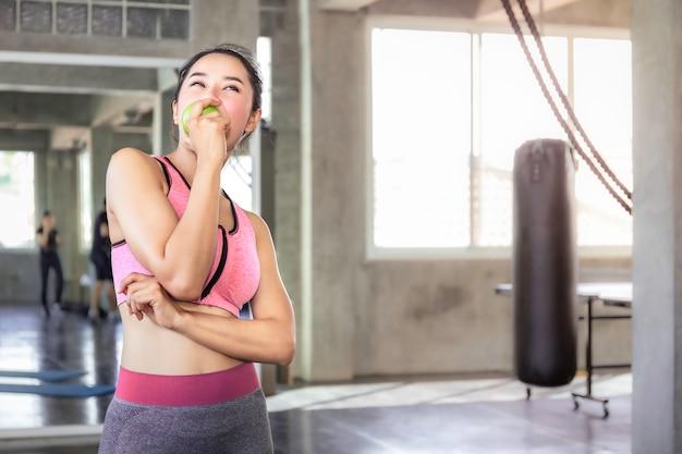 Perfekte asiatin in der sportkleidung, die grean apfel für hält, essen vor training an der eignungsturnhalle.