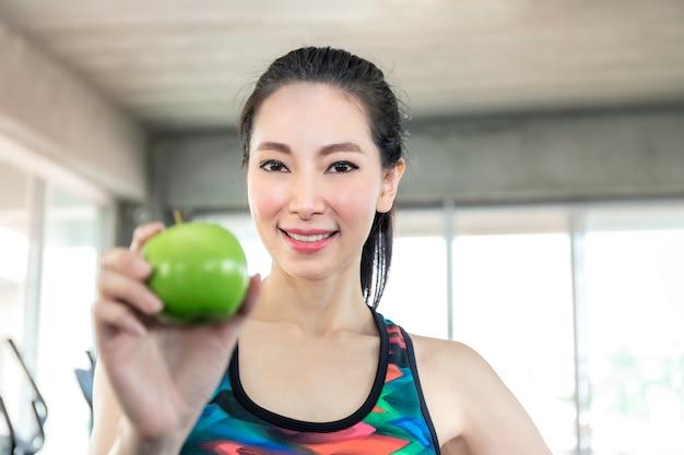 Perfekte asiatin in der sportkleidung, die grünen apfel für hält, essen vor training an der eignungsturnhalle.