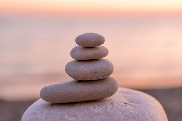 Perfekte balance des stapels kiesel an der küste in richtung zum sonnenuntergang