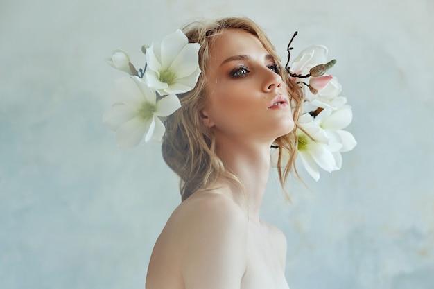 Perfekte braut mit juwelen, ein porträt eines mädchens in einem langen weißen kleid. schönes haar und saubere zarte haut. hochzeitsfrisur blonde frau. mädchen mit einer weißen blume in ihren händen