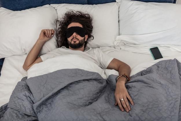 Perfekte entspannung. netter schläfriger mann, der auf seinem bett liegt, während er eine schlafmaske trägt