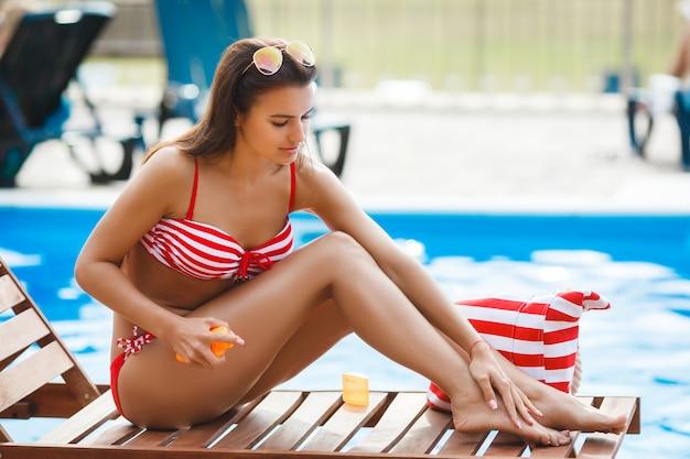 Perfekte frau in der nähe des schwimmbades. junges schönes mädchen, das sonnenbad hat. hübsche frau, die am strand entspannt