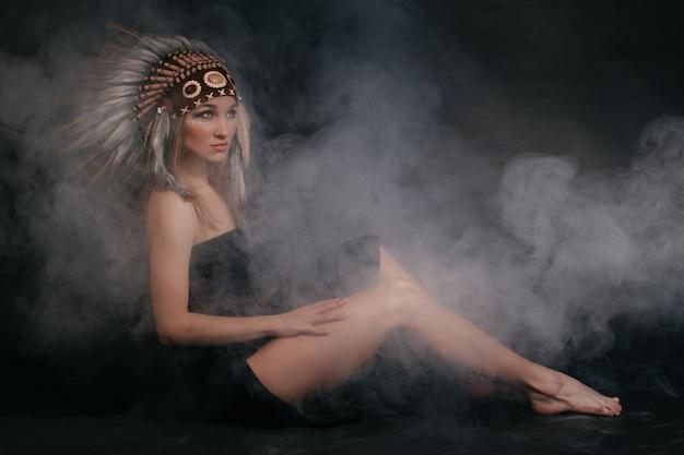 Perfekte frau in der tracht indianer in rauch auf einem grauen hintergrund