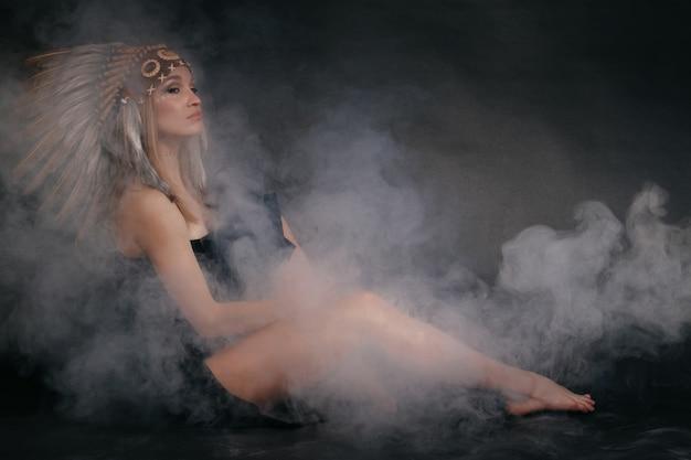 Perfekte frau in tracht der indianer in rauch auf grau