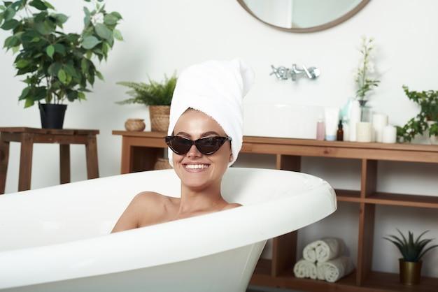 Perfekte frau mit weißem handtuch auf kopf nach der dusche, die zahniges lächeln hat