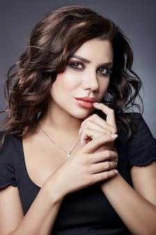Perfekte gesichtshaut, schönes make-up, hautpflege. mode-luxus-schönheitsfrauen-nahaufnahme-porträt auf schwarzem hintergrund. brünette mit lockigem haar kunst