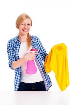 Perfekte hausfrau, die den fleck mit hemden reinigt