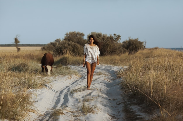 Perfekte junge boho-frau, die in voller länge auf einem tropischen sandstrand gegen schönes bokeh geht