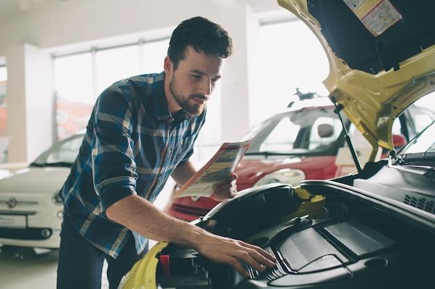 Perfekte linien. der junge dunkelhaarige bärtige mann untersucht das auto im autohaus und trifft seine wahl. horizontales porträt eines jungen kerls am auto. er überlegt, ob er es kaufen soll.