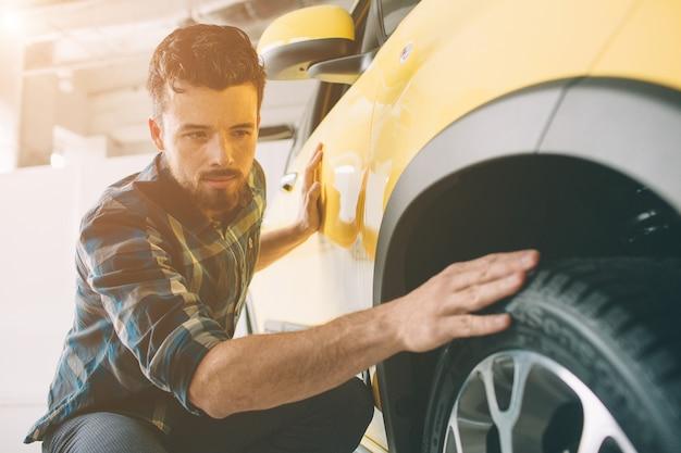 Perfekte linien. der junge dunkelhaarige bärtige mann untersucht das auto im autohaus und trifft seine wahl. horizontales porträt eines jungen mannes am auto. er überlegt, ob er es kaufen soll.