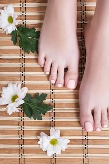 Perfekte nude-pediküre an den zehen. weibliche füße mit pastellgelpolitur-draufsicht auf hölzernem hintergrund. ergebnis des spa-salon-verfahrens