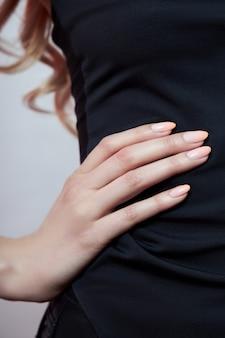 Perfekte rosa maniküre an den fingern einer frau. glatte, saubere haut der hände