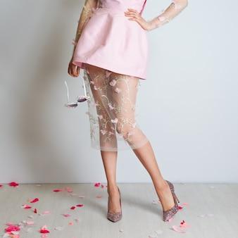 Perfekte schlanke lange weibliche beine und rosa kleid