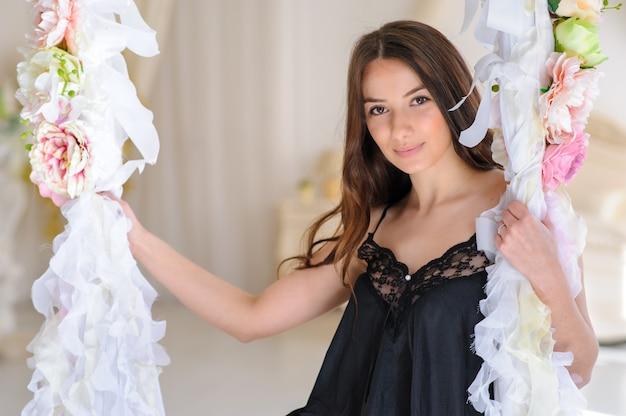 Perfekte sexy bräunungsfrau mit perfekter haut, großen vollen lippen, die im schlafzimmer aufwerfen und sexy luxus stilvolle schwarze dessous tragen. eine dame posiert auf einer schaukel in ihrer wohnung.