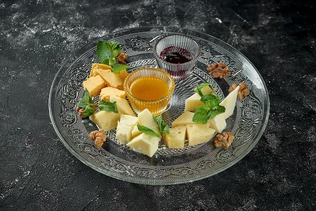 Perfekte vorspeise - verschiedene hausgemachte käsesorten mit honig und nüssen auf einem transparenten teller auf einem dunklen tisch