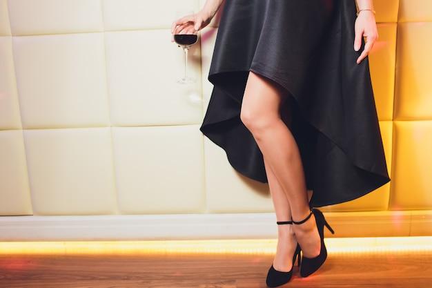 Perfekte weibliche beine, die hohe absätze und schwarzes kleid tragen.
