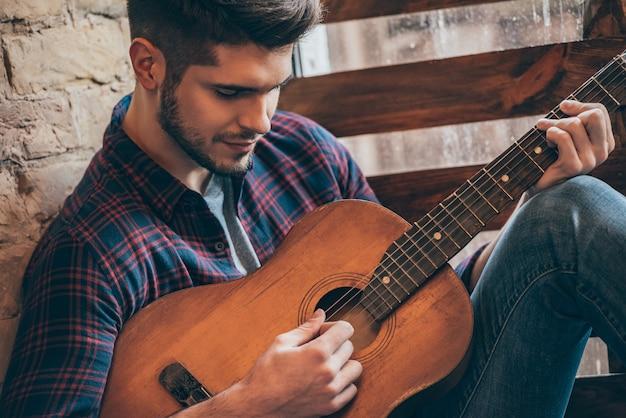 Perfekter akkord. nahaufnahme eines gutaussehenden jungen mannes, der gitarre spielt, während er auf der fensterbank sitzt