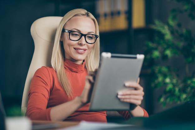 Perfekter anführer großer firmeninhaber charmante frau sitzen stuhl tisch verwenden tablet-suche moderne start-up-entwicklung nachrichten mitarbeiter ausbildung in büro loft tragen roten rollkragenpullover