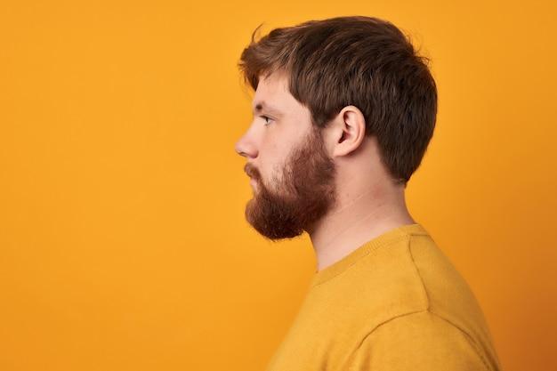 Perfekter bart. nahaufnahme des jungen bärtigen mannes, der gegen gelben isolierten hintergrund steht.