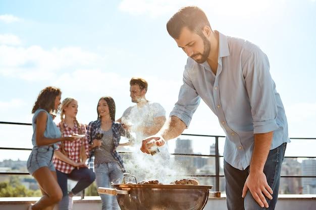 Perfekter fleischgrill junger bärtiger mann, der fleisch auf dem grill grillt, während er auf dem steht