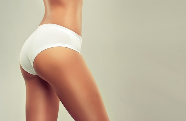 Perfekter frauenkörper im weißen sporthöschen enge taille und gebräunte haut körper- und hautpflege