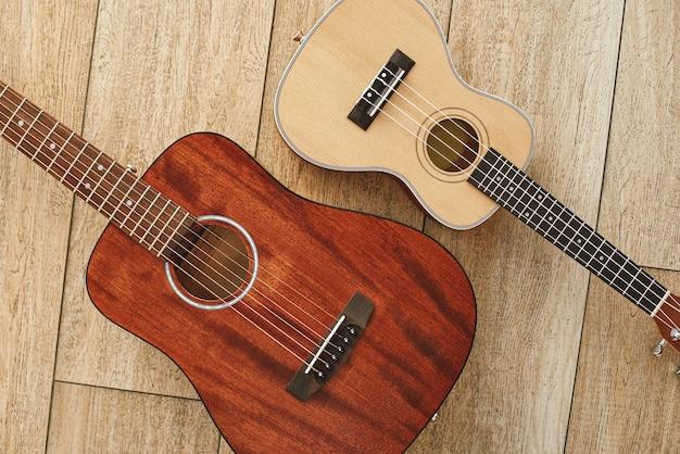 Perfekter klang. draufsicht auf die nahe beieinander liegenden akustik- und ukulele-gitarren auf dem holzboden. musikkonzept. musikinstrumente