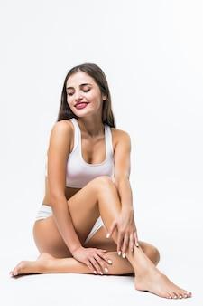 Perfekter körper, schöne frau. modell mädchen mit schönen körper - beine, arme, schultern, auf einem boden sitzend. gesundheits- und schönheitsfrau in der weißen unterwäsche, die ihre haut berührt.