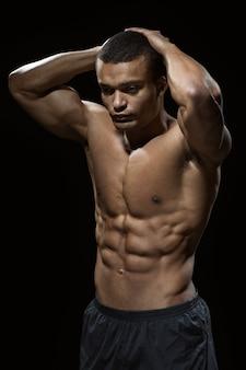 Perfekter körper. vertikale aufnahme eines afrikanischen mannes mit getöntem körper, der hemdlos im studio aufwirft