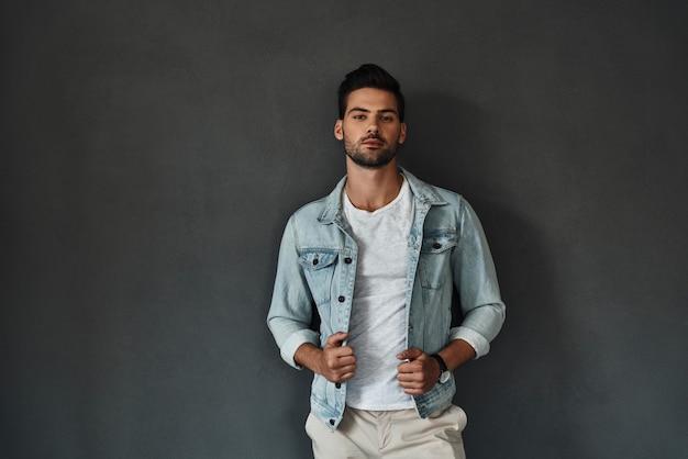Perfekter mann. hübscher junger mann, der die kamera anschaut und seine jeansjacke anpasst, während er vor grauem hintergrund steht