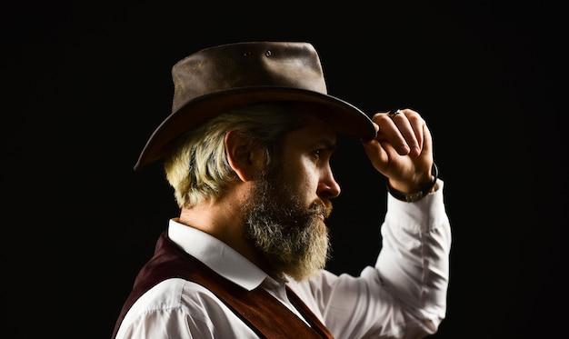 Perfekter rüde. detektivische bestätigung oder begrüßung. trilby-hut. mann im vintage-stil mit breiter krempe. mann mit retro-hut. brutaler bärtiger hipster in anzugweste. mafia gentlemen club. reifer cowboy.