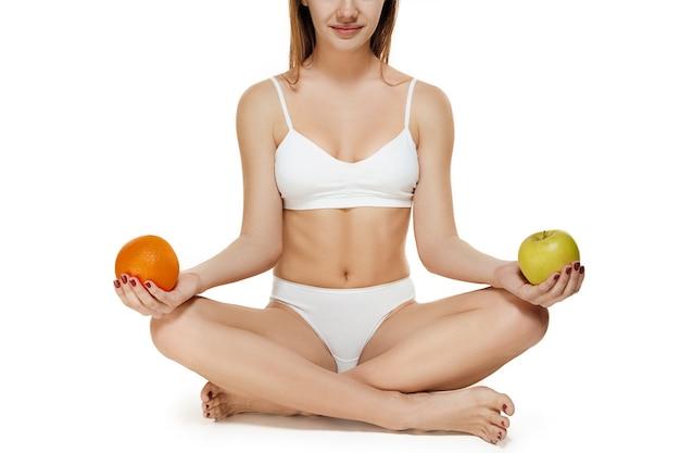 Perfekter schlanker junger körper des mädchens oder der fitten frau, die im studio mit früchten sitzt. das konzept für fitness, ernährung, sport, plastische chirurgie und ästhetische kosmetik. das bild ist nicht retuschiert