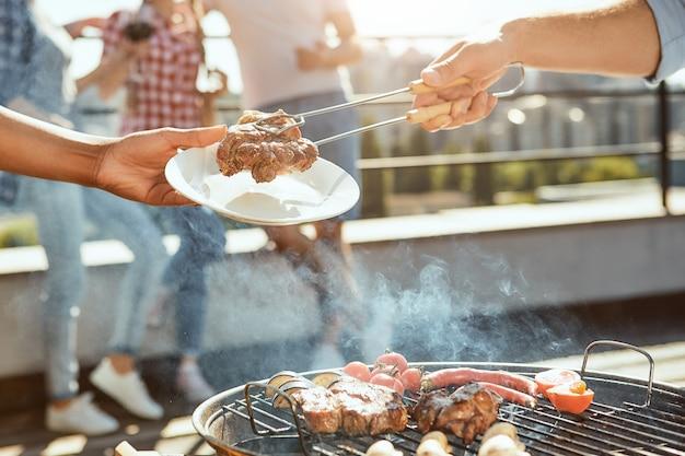 Perfekter tag für grillbeschnittenes foto der männlichen hand, die heißes gegrilltes fleisch auf die