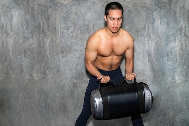 Perfektes athletisches asiatisches manntraining mit energietasche an der turnhalle.