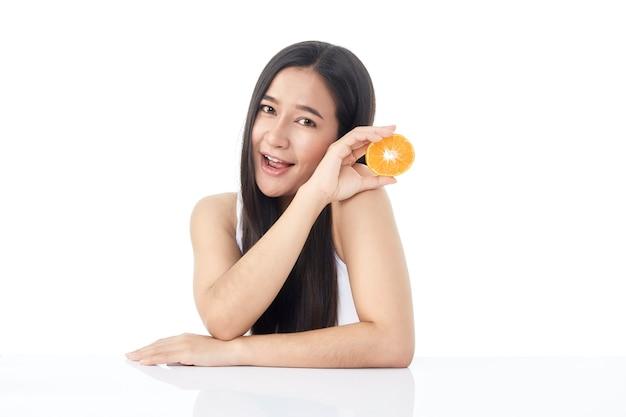 Perfektes frisches hautporträt des jungen asiatischen schönen mädchens mit orangenscheiben in der hand lokalisiert auf weißem hintergrund