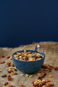 Perfektes frühstück. gesunde frühstückszerealien mit nüssen, kürbiskernen, hafer und in schüssel auf isoliert. gesunder snack oder frühstück am morgen.