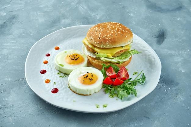 Perfektes frühstück - hühnchen-käse-burger, 2 spiegeleier und salat mit rucola und kirschtomaten auf einem weißen teller